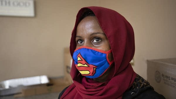 A person wears a Superman mask.