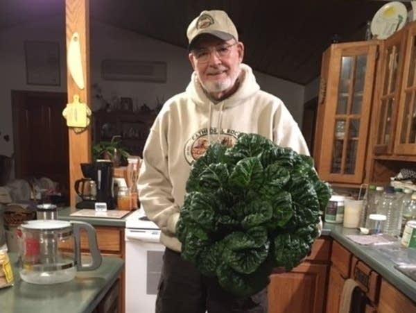 Groshed owner Ron Kidder holds a big head of lettuce.