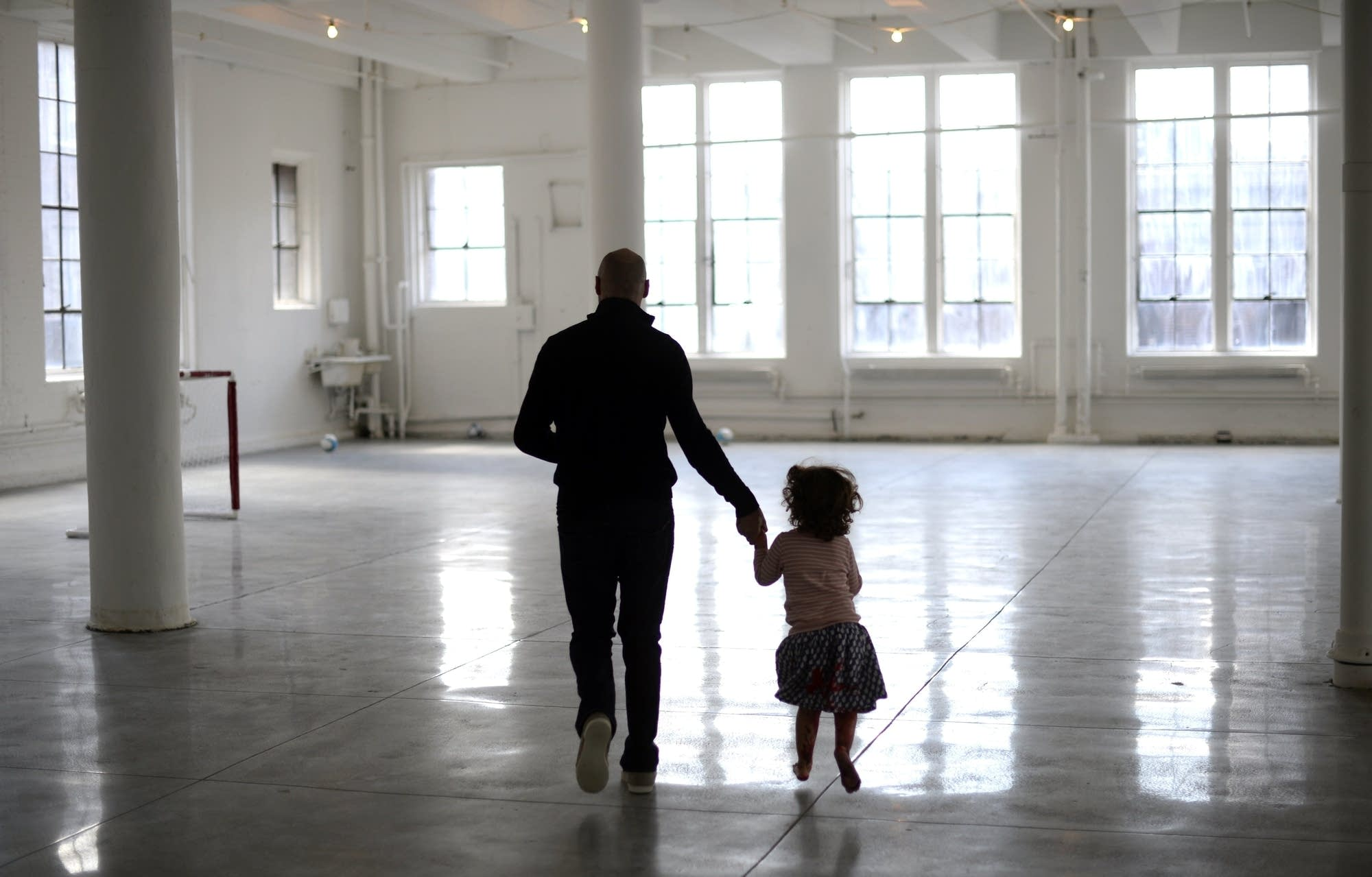 A dad runs with his daughter in the kid's play area during an event