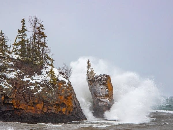Waves crash around a sea stack