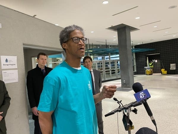 A man speaks in front of microphones at a transit hub.
