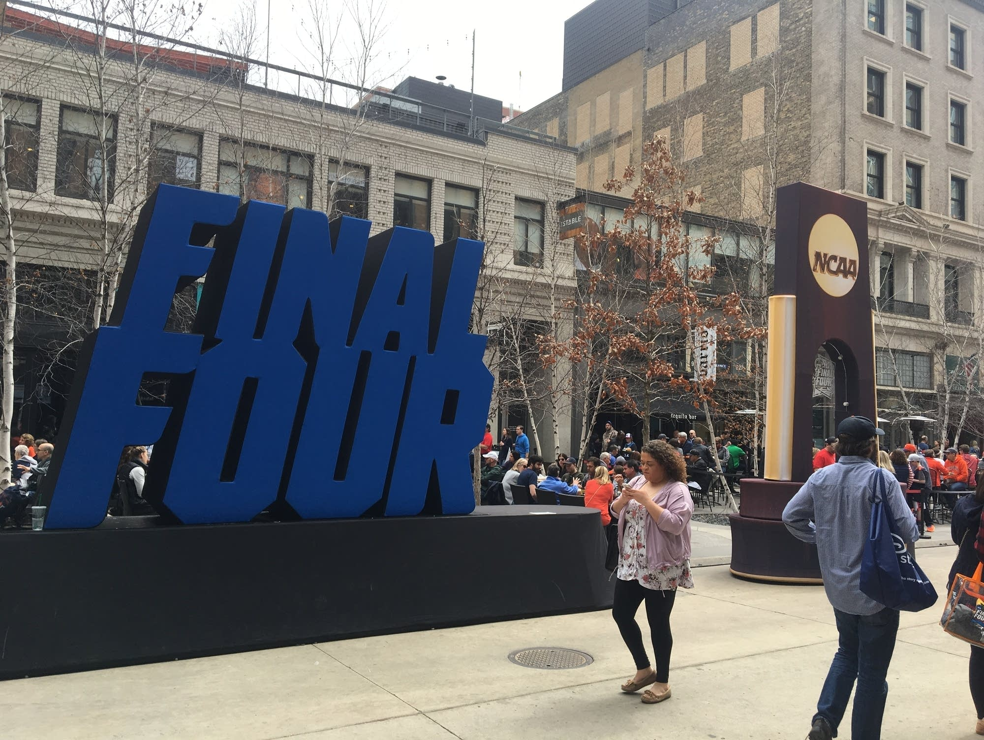 People walk in front of a 3D Final Four sign on Nicollet Mall