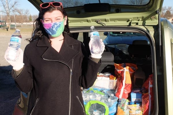 A person holding bottles of water in front of a car.