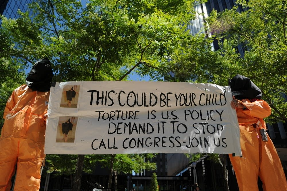 Protesters hold a sign opposing U.S. torture