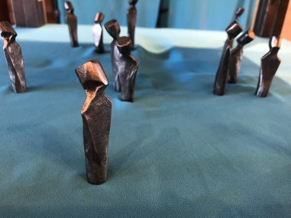 Small humanoid-shaped sculptures stand on a blue cloth.