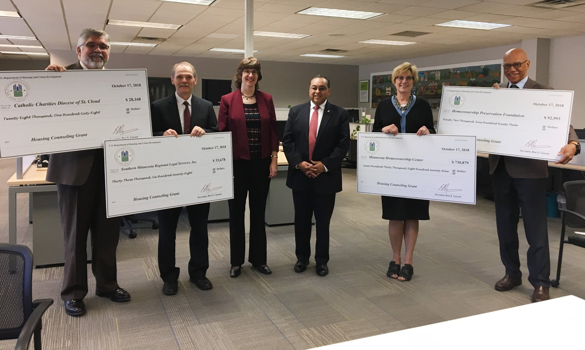 Representatives hold up checks at the Minnesota Homeownership Center