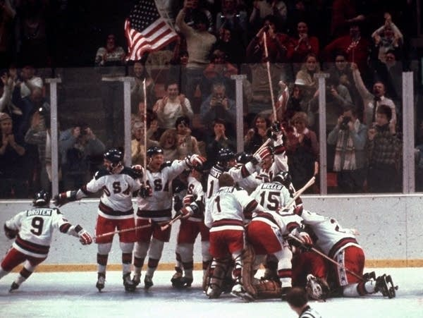 The U.S. men's hockey team pounces on goalie Jim Craig