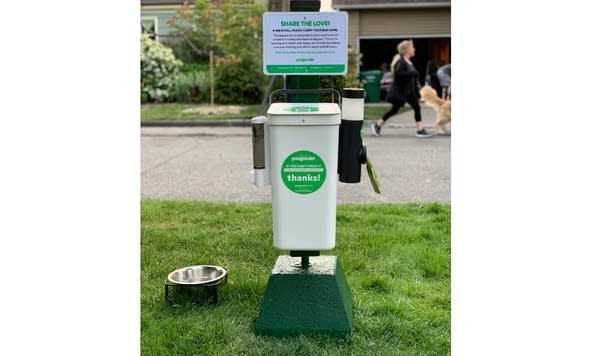 """Photo of a """"PooGooder"""" garbage bin for dog poop, outside on green lawn"""