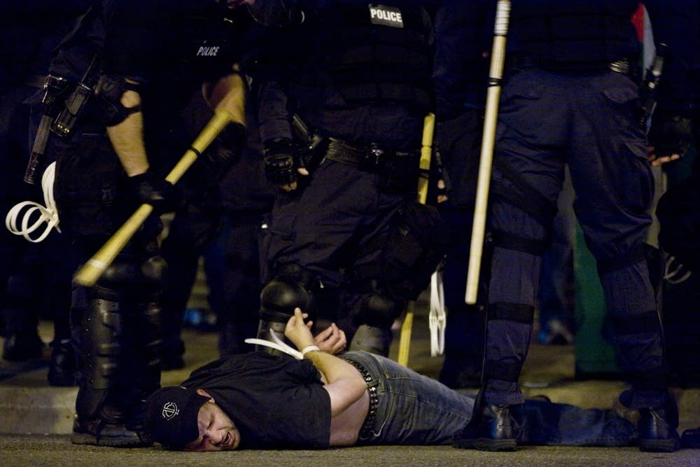 Police arrest a protester outside the concert