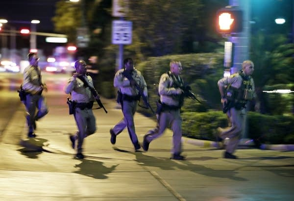 Police run to cover at the scene of a shooting near Mandalay Bay.