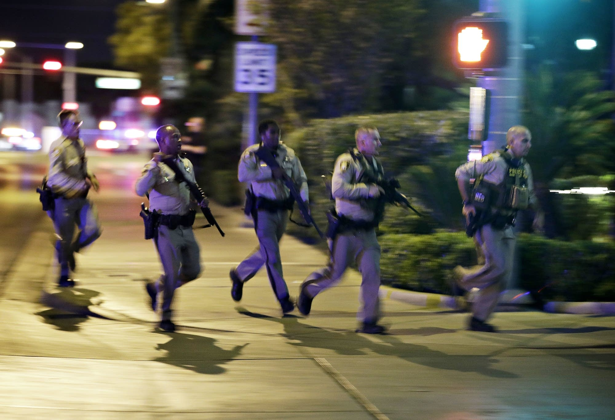 Police run to cover the scene of a shooting near Mandalay Bay.