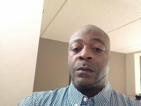 A man in a checkered shirt takes a selfie.