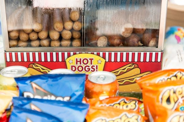 Hot dogs and bratwursts sit in a steamer on the counter.