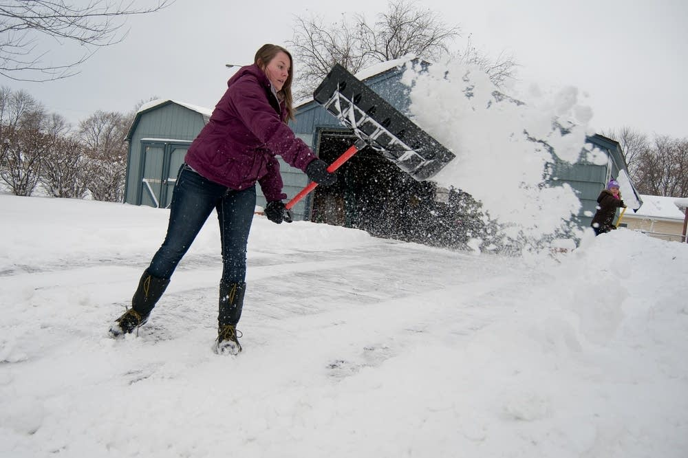 Haley Meyer throws a shovel full of snow.