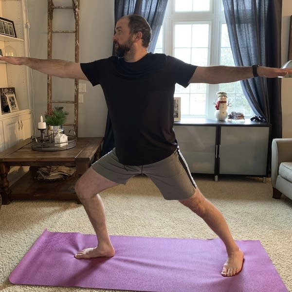 A man does yoga exercises at his home in Rogers, Minn.