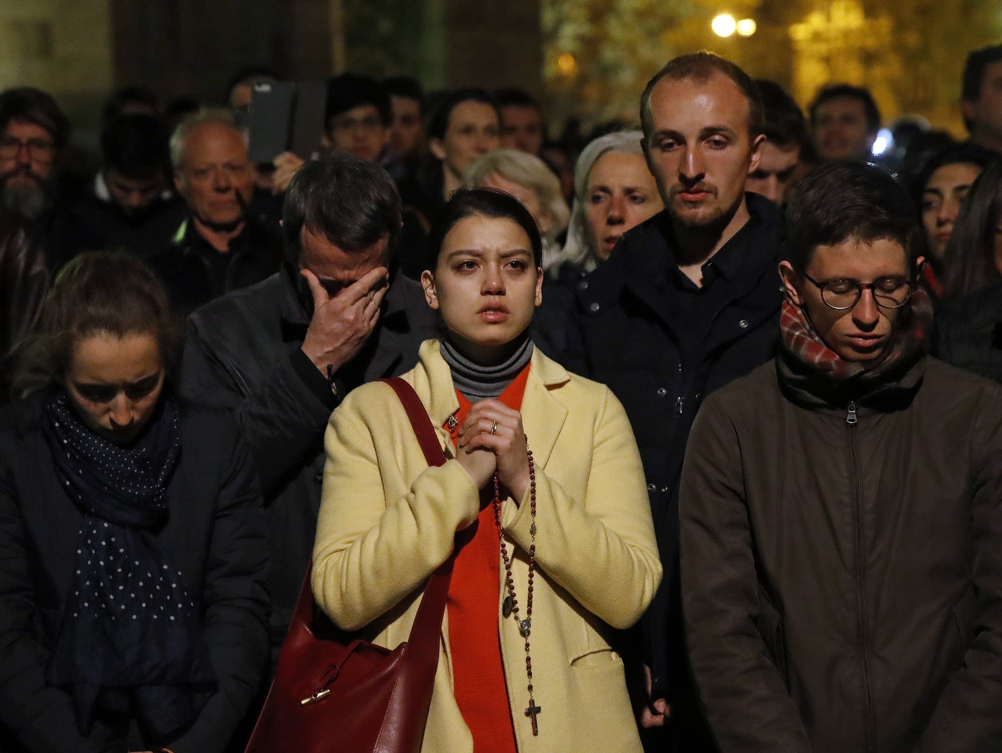 People pray as Notre Dame cathedral burns in Paris Monday, April 15, 2019.