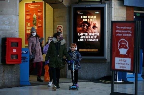 People in masks walk outside a train station.