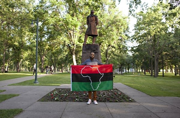 Organizer and activist Wess Philome holds the Pan-African flag