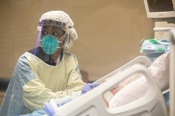 A person in PPE stands at a bed of a patient.