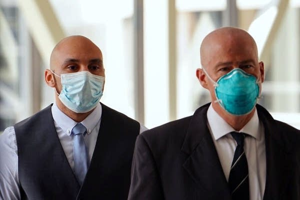 Two people wearing face masks.