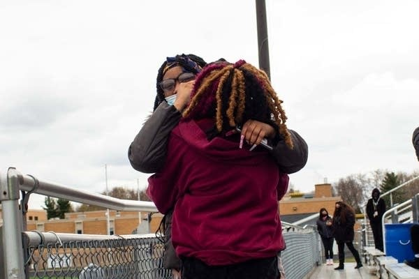 Two students hug each other.