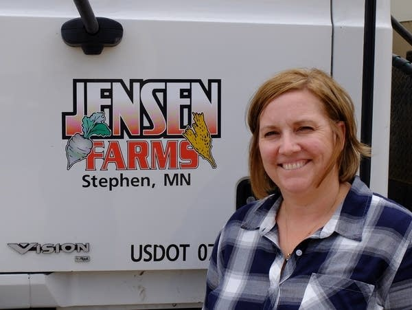 Betsy Jensen stands near one of the farm trucks parked at the family farm.