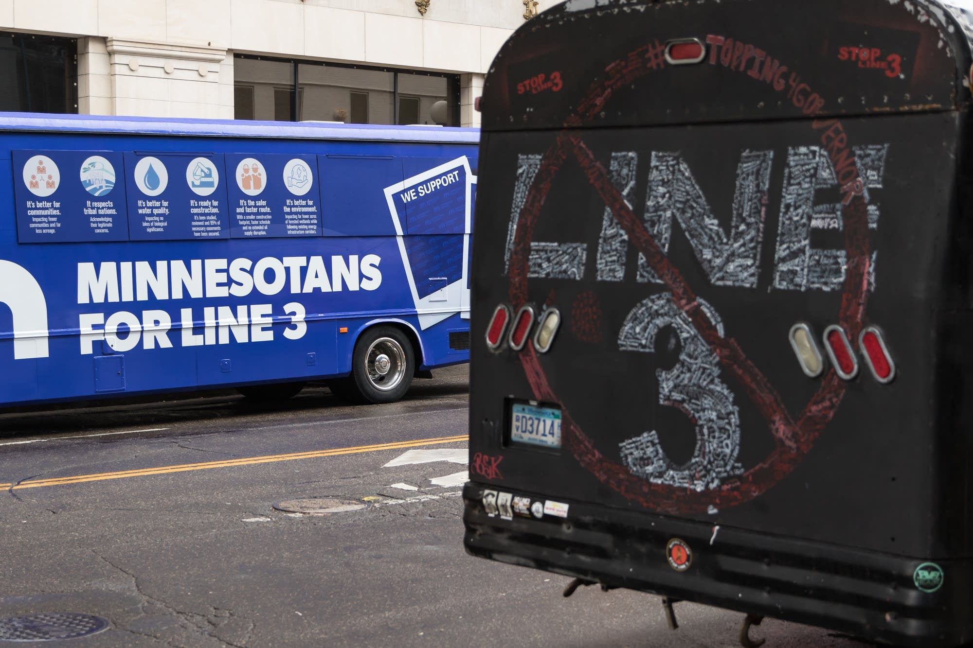 Line three proponents and opponents' buses sit across the street.
