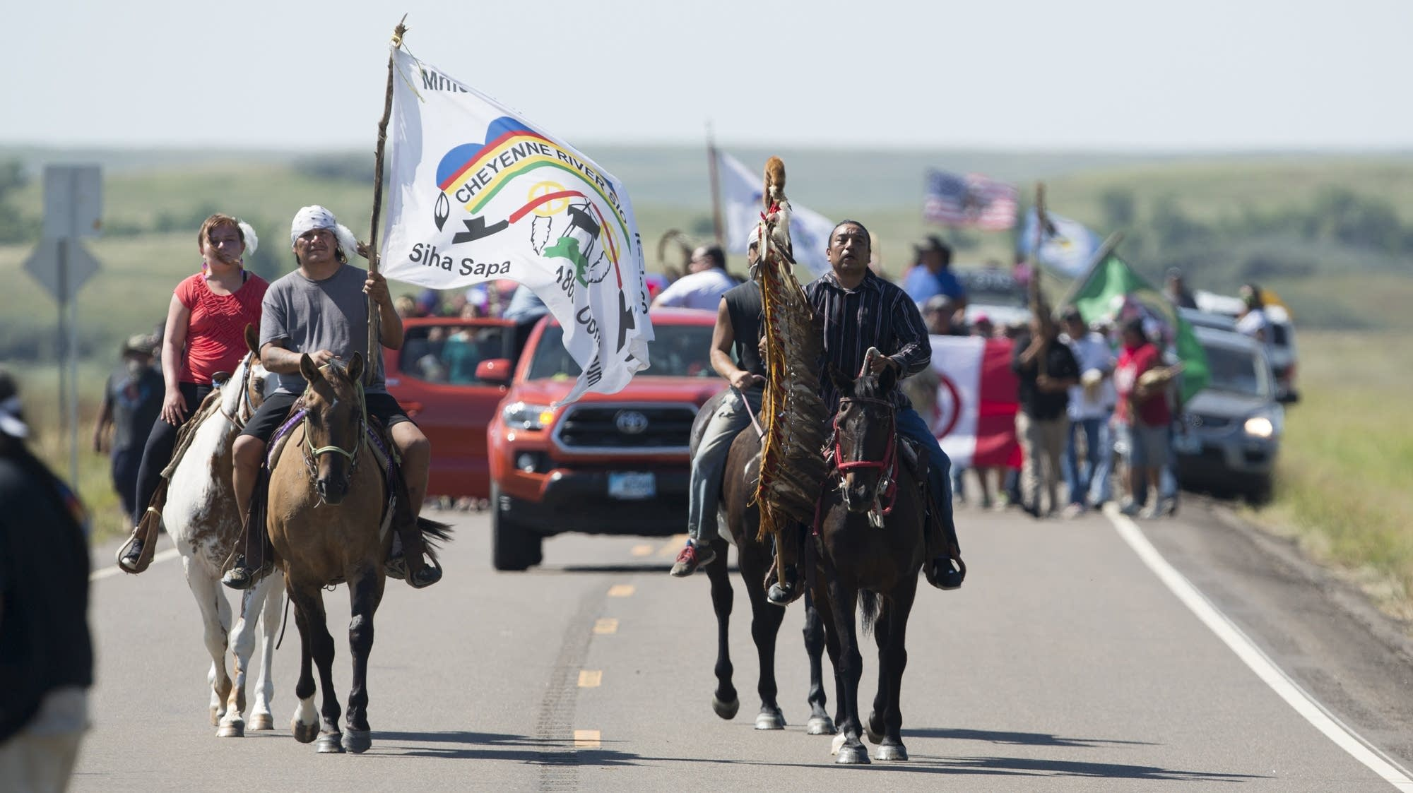 Protesters march and ride from the camp.