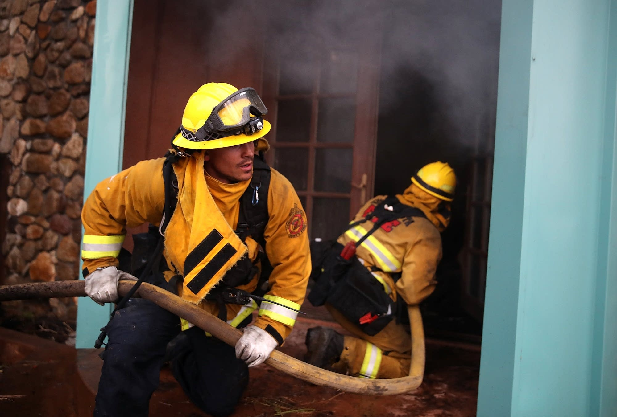 Firefighters try to extinguish a house fire.
