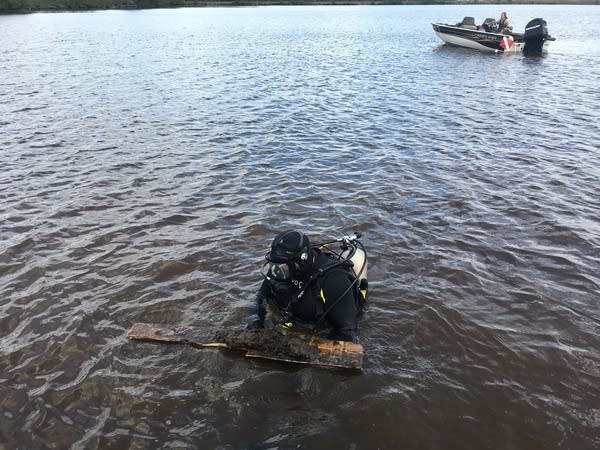 Minnesota DNR divers recover submerged lumber from a river