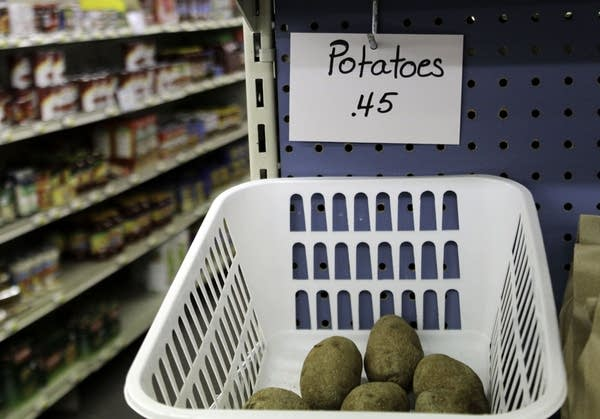 A white bin attached to a blue shelf filled with potatoes.
