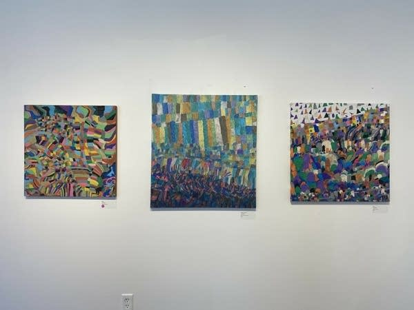 Paintings hang on a gallery wall.