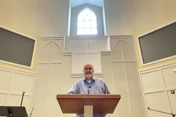 A pastor stands in a church.