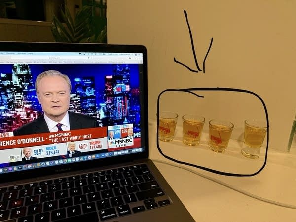 Laptop computer playing MSNBC News next to 4 shots of whiskey