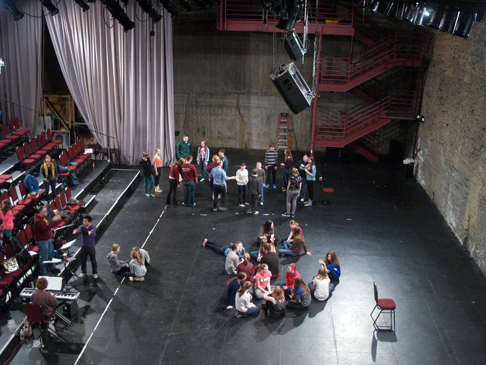 Cast members wait for rehearsal to begin.