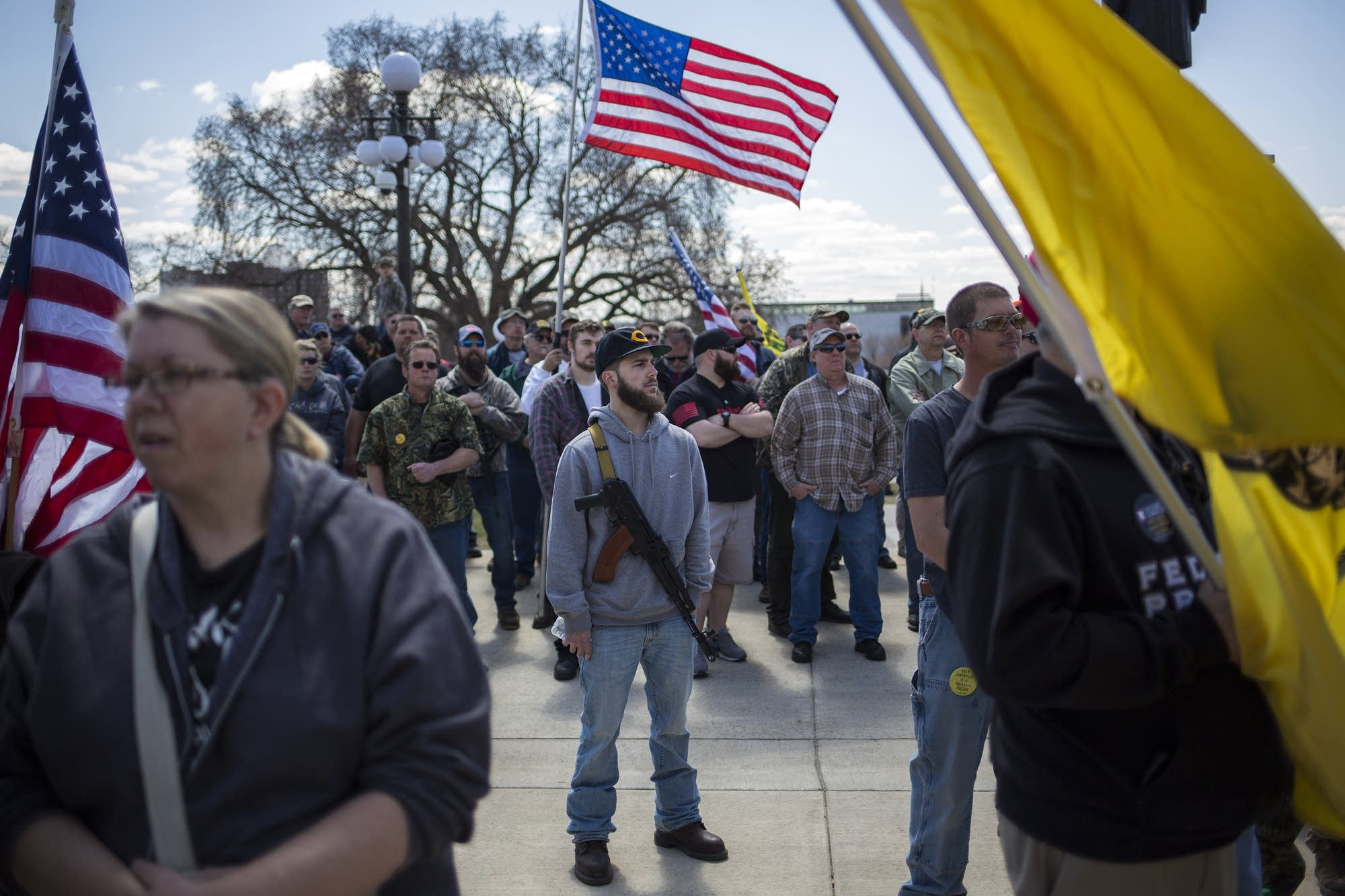 A man who asked not to be identified, center, carries a firearm.