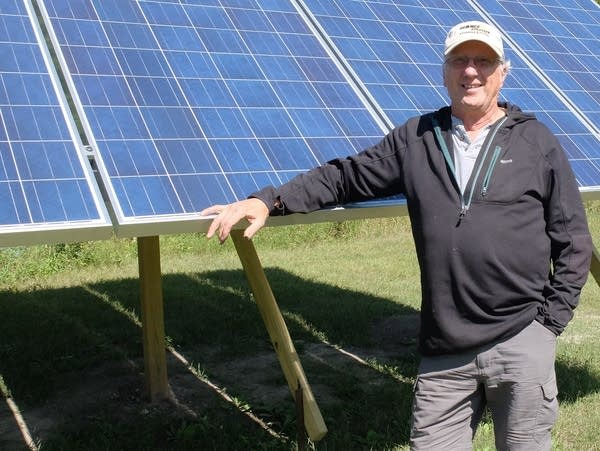 Dan Juhl stands near a solar panel