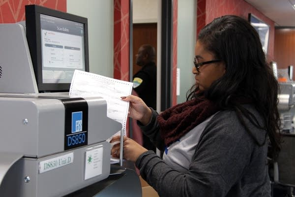 Jalisa Moore puts a stack of ballots into the counting machine.