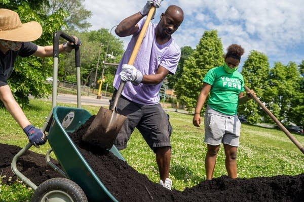 Two people shovel dirt into a wheelbarrow.