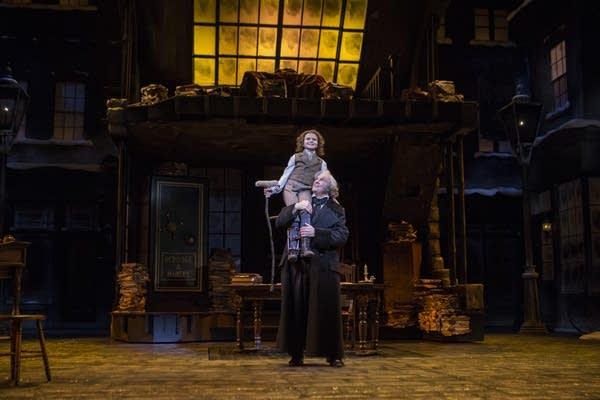 Ebenezer Scrooge lifts Tiny Tim during the closing scene.