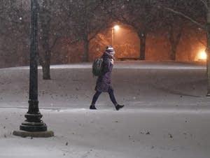 A woman walks across the snowy University of Minnesota campus.