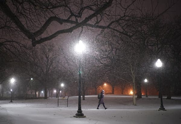 A woman walks across the snowy University of Minnesota campus.