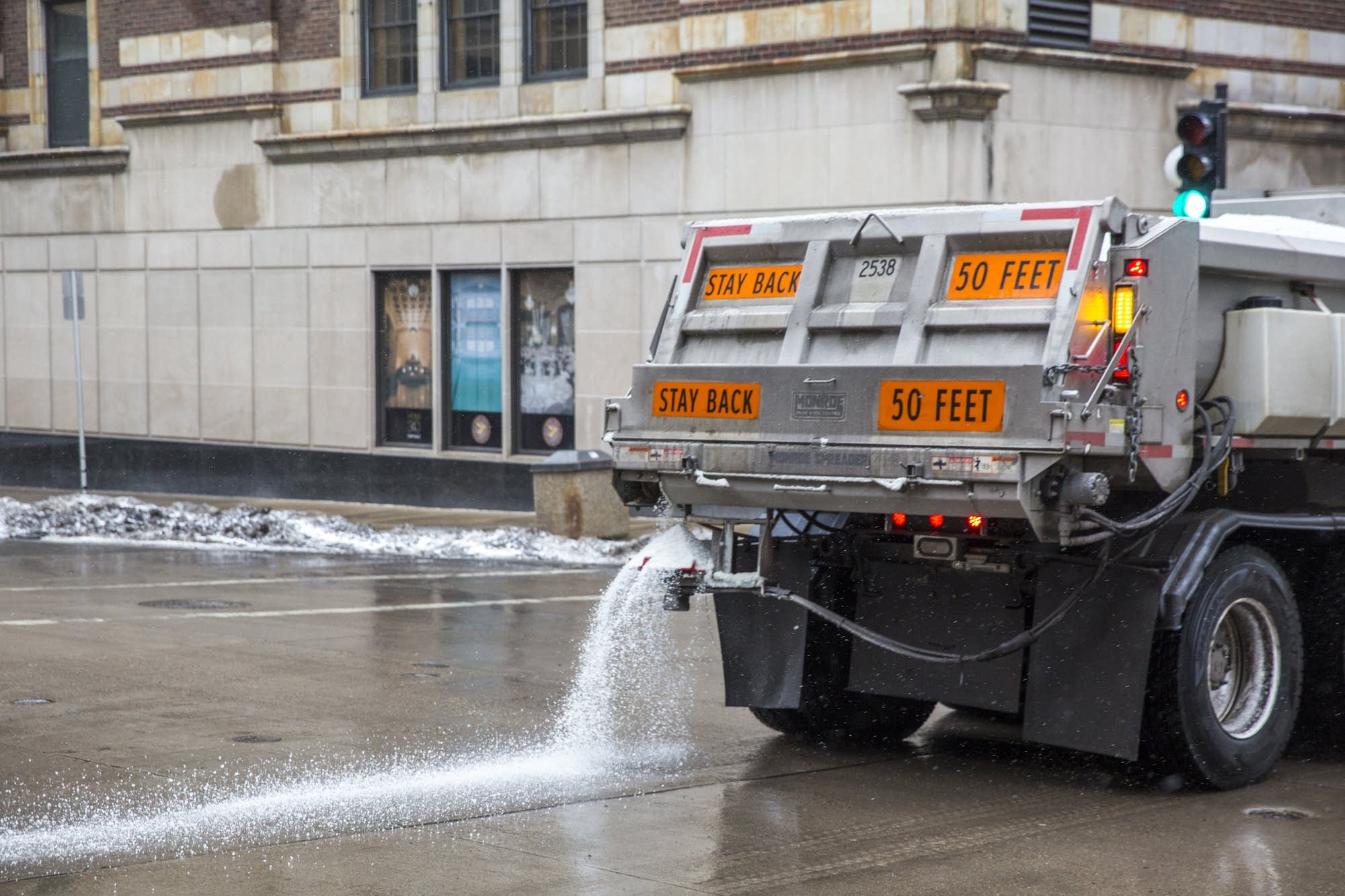 A snow plow lays down road salt in downtown St. Paul, Minn.