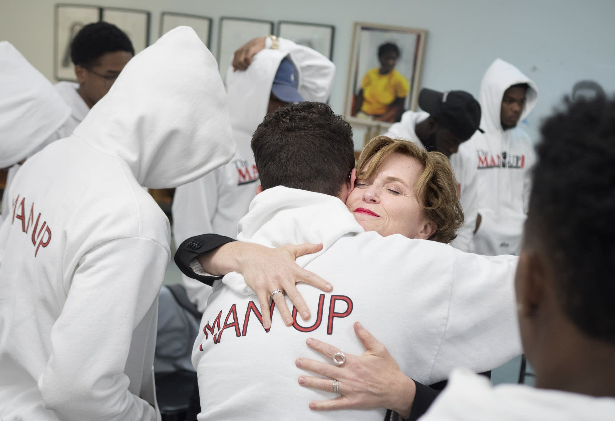 Mayor Betsy Hodges embraces members of The Man Up Club.