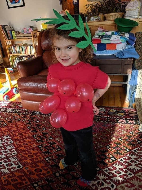 A child with balloons pinned to her shirt to look like berries.