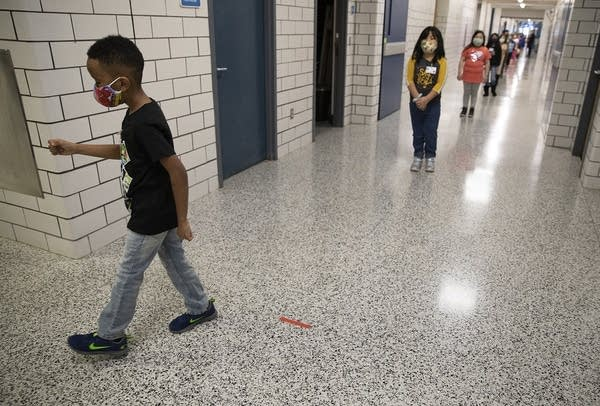 Kids space apart while they walk in hallway