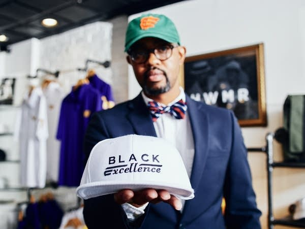 A man holds a white baseball cap with the words 'Black Excellence'.