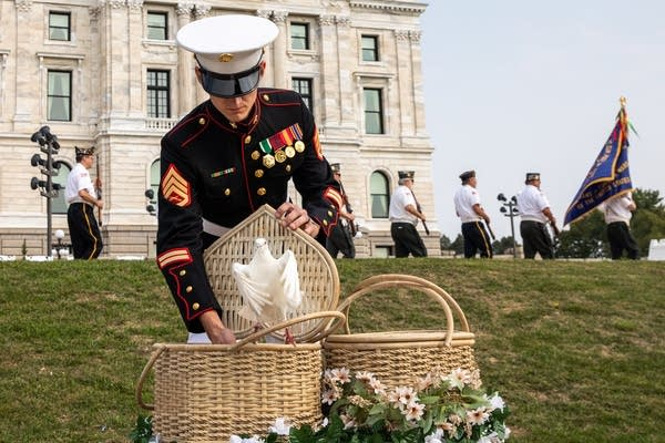 A Marine releases doves from a basket.