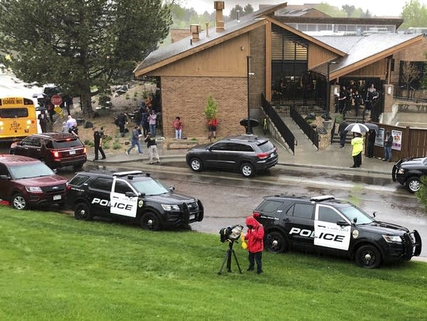 Police and others are seen outside STEM School Highlands Ranch