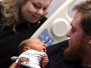 Andrew Goette and his wife, Ashley, look at their baby, Lennon.